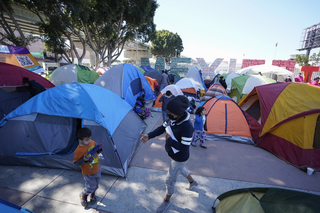 """People walk among tents crowded next to large letters reading """"Mexico"""" in green, white and red."""