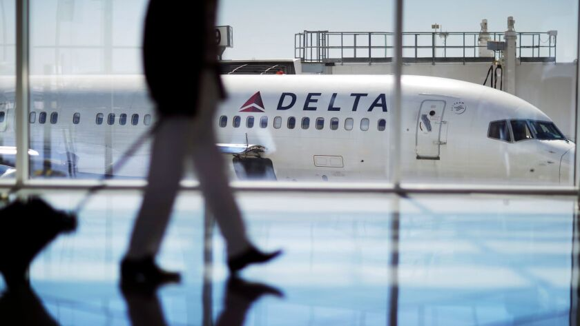 FILE - In this Oct. 13, 2016 file photo, a Delta Air Lines jet sits at a gate at Hartsfield-Jackson