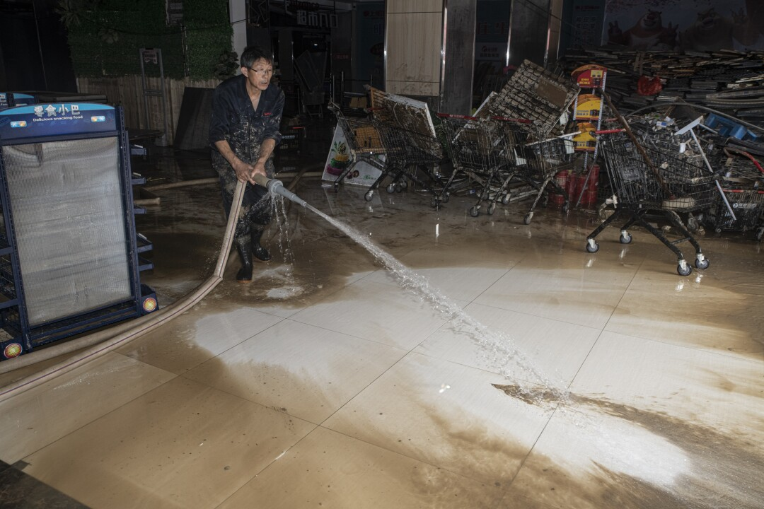 An employee washes away mud from the floor of a flooded supermarket in Shexian, Anhui province.
