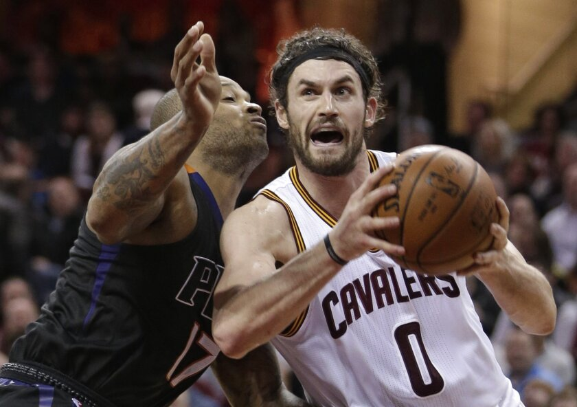 FILE - In this Jan. 27, 2016, file photo, Cleveland Cavaliers' Kevin Love, right, drives past Phoenix Suns' P.J. Tucker during the second half of an NBA basketball game, in Cleveland. The Cleveland forward has heard his name in trade rumors for much of the season. (AP Photo/Tony Dejak, File)