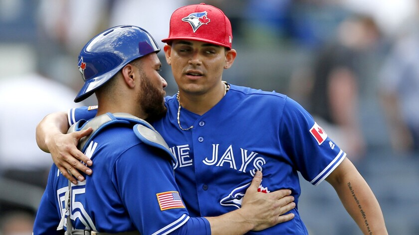 Blue Jays closer Roberto Osuna celebrates with catcher Russell Martin after a 4-1 victory over the Yankees earlier this season.