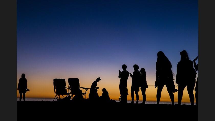 Beachgoers are cast in silhouette on Santa Monica Beach in November 2017.