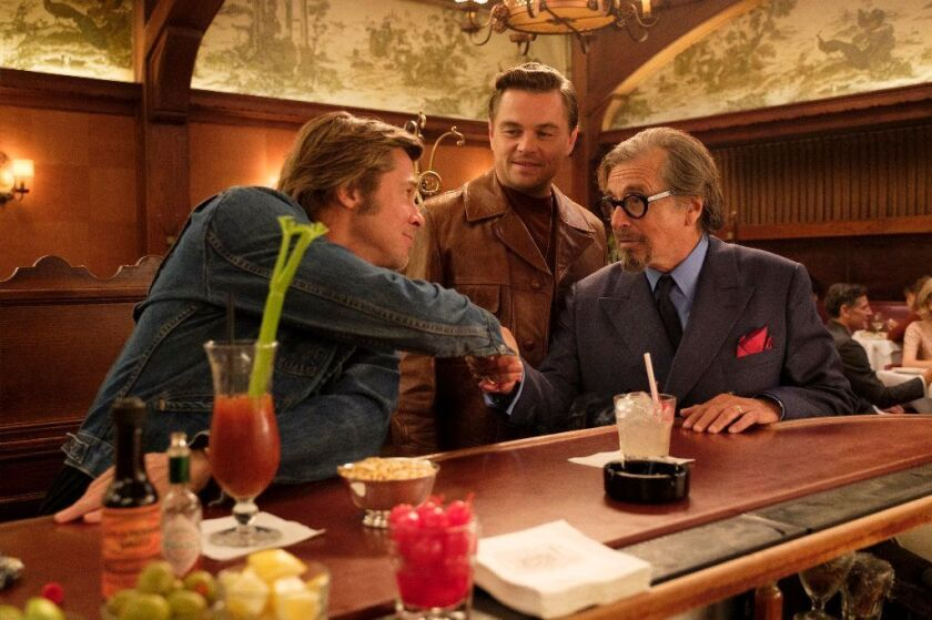 Brad Pitt, left, and Al Pacino shake hands, sitting at the bar at Musso & Frank Grill, with Leonardo DiCaprio standing between them.