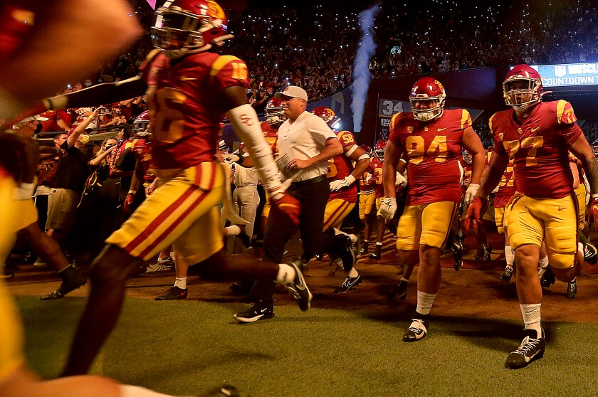 USC coach Clay Helton runs onto the field at the Coliseum with his players before losing to Stanford on Saturday.