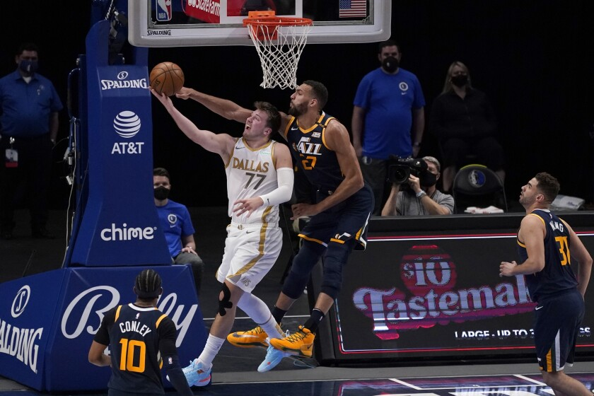 Dallas Mavericks guard Luka Doncic (77) goes up to shoot as Utah Jazz center Rudy Gobert, center right, defends in the first half of an NBA basketball game in Dallas, Monday April 5, 2021. Jazz's Mike Conley and Georges Niang look on. (AP Photo/Tony Gutierrez)