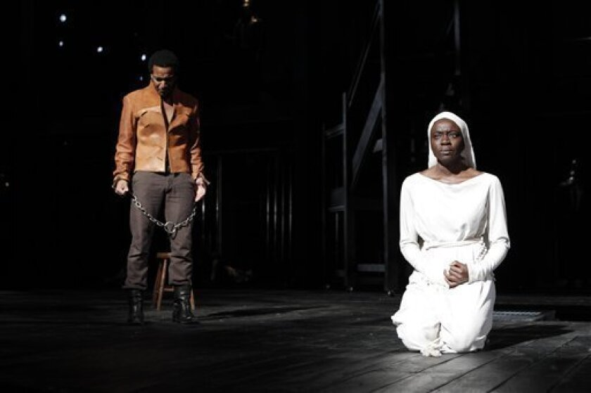 """In this theater publicity image released by The Public Theater, André Holland, left, and Danai Gurira, are shown during a performance of """"Measure for Measure,"""" in New York. (AP Photo/The Public Theater, Joan Marcus)"""