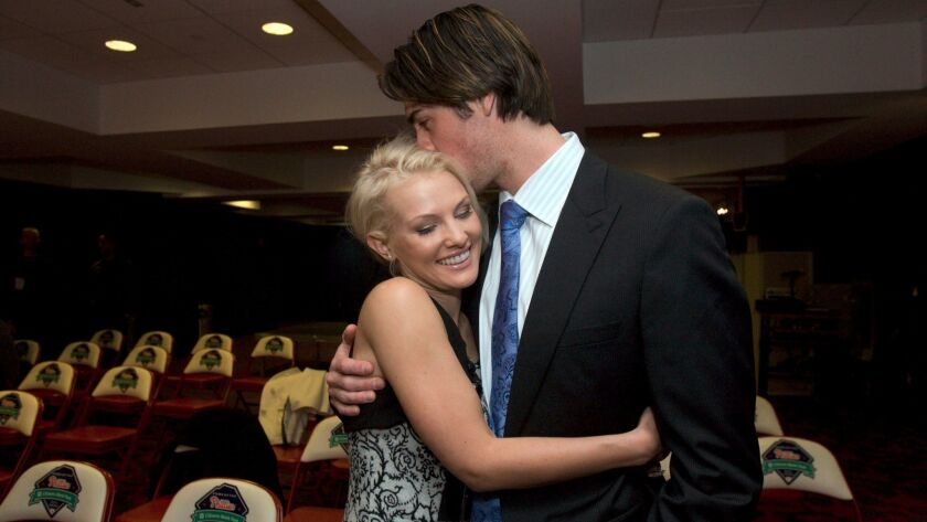 Cole Hamels gets a hug from his wife, Heidi Hamels, following a 2009 news conference at Citizens Bank Park in Philadelphia.