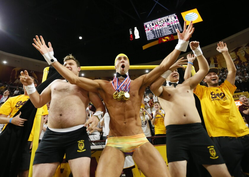 Olympic swimmer Michael Phelps, center, takes part in Arizona State's Curtain of Distraction during an Oregon State free throw on Thursday night.