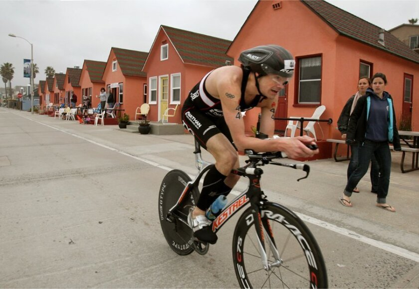 Overall winner Andy Potts speeds by historic Roberts Cottages on The Strand with no other competitors in sight behind him during the bicycle portion of the event. He was the first competitor in the swim, bike, and run. He also won it last year.