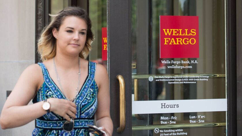 A woman walks out of a Wells Fargo bank in Washington, DC, on May 27, 2016. Wells Fargo is heavily l
