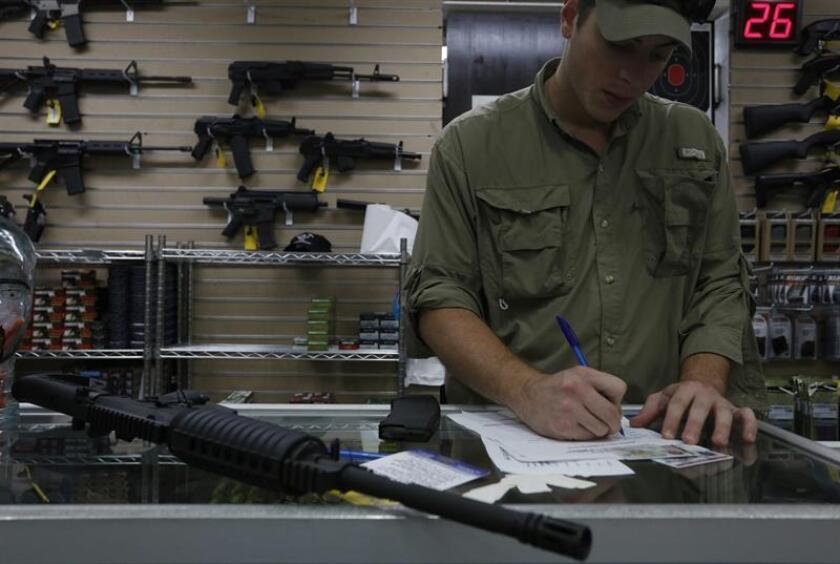 Vista de una persona que vende una AR15 calibre 223 a un civil, en una armería en San Juan. EFE/Archivo