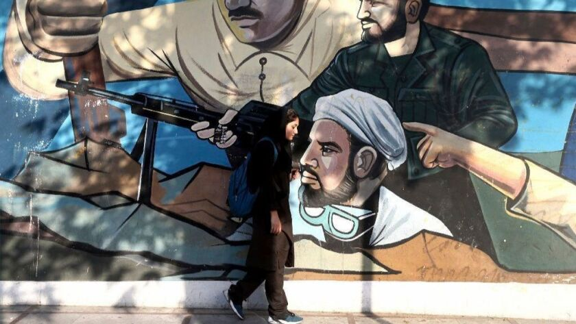 A woman walks past a mural depicting Iranian war heroes in downtown Tehran.