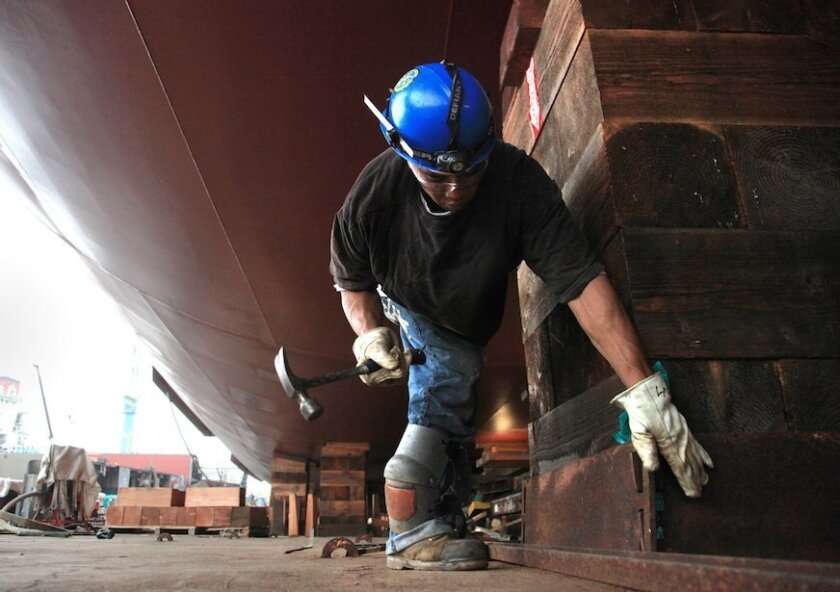 A NASSCO worker removes some of the support blocks the TOTE 2 containership sat on during construction. The ship will settle on to a moving sled, or way, that will carry the 764-foot vessel into San Diego Bay.