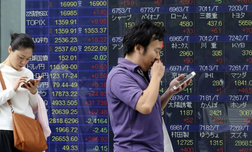 People look at their cell phone in front of an electronic stock board of a securities firm in Tokyo, Monday, May 30, 2016. Asian stocks rose Monday following Wall Street's gains as investors looked ahead to economic data this week from China, Australia and Korea. (AP Photo/Koji Sasahara)