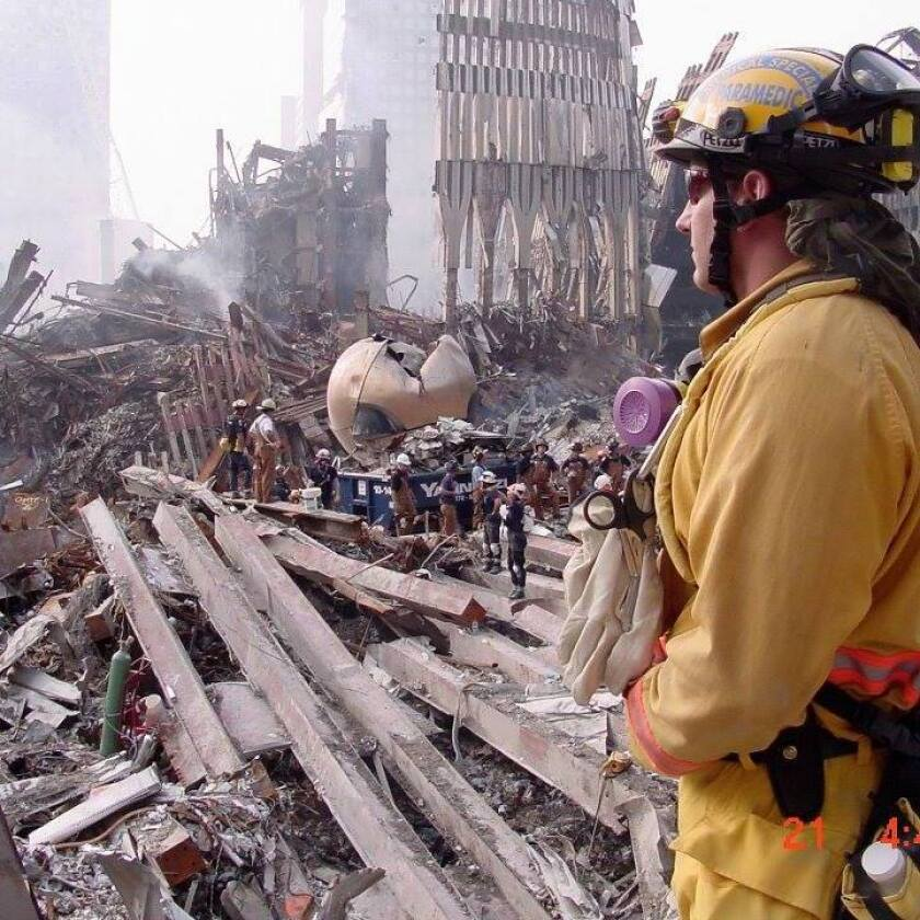 California Task Force Eight firefighter at Ground Zero overlooking a fallen World Trade Center tower.