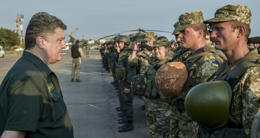 Ukrainian President Petro Poroshenko, left, inspects military personnel during his visit to the southeastern coastal town of Mariupol on Sept. 8.