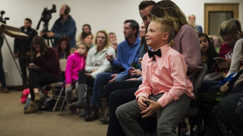 Third-grader Dane Best sits on his mother's lap before urging town leaders in Severance, Colo., to lift a ban on throwing snowballs.