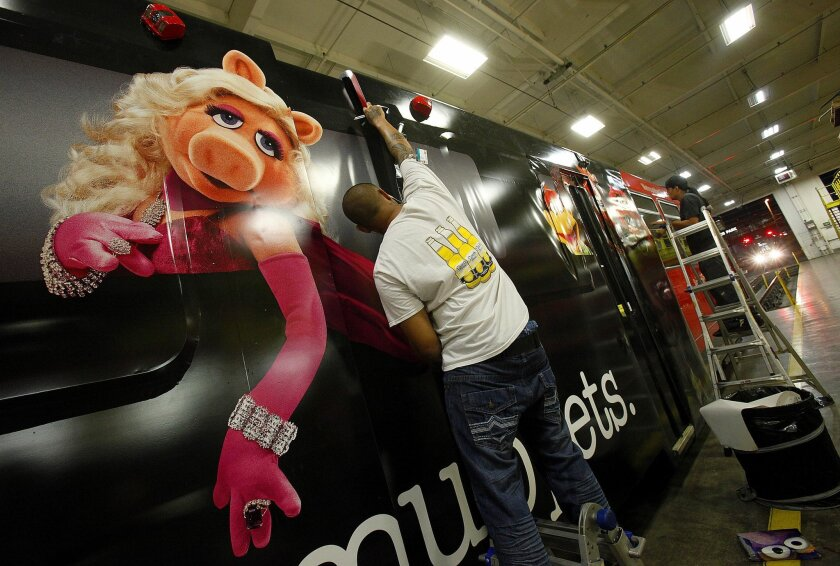 Graphics installer Shaun Shepard works on wrapping a San Diego Trolley with a Muppets theme during overnight work  in advance of Comic-Con.