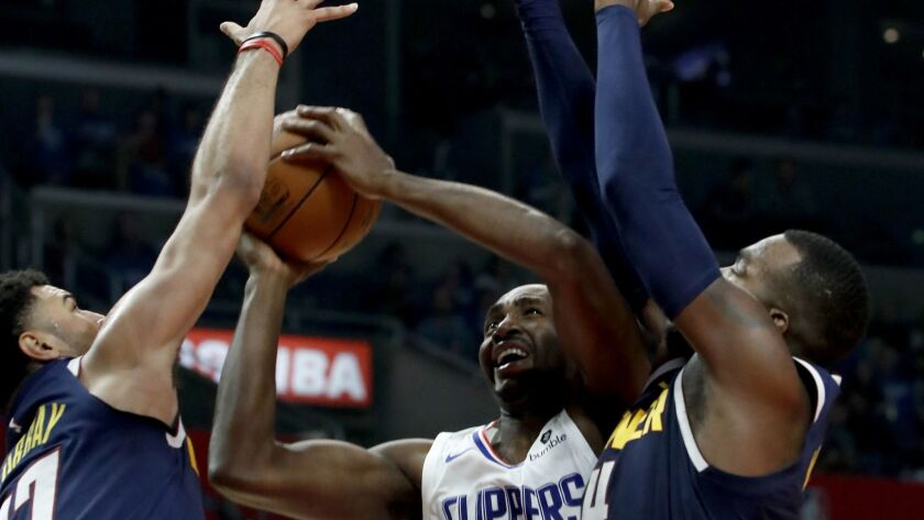 The Clippers' Luc Mbah a Moute goes up for a shot against the Nuggets' Jamal Murray, left, and Paul Millsap on Oct. 17 at Staples Center.