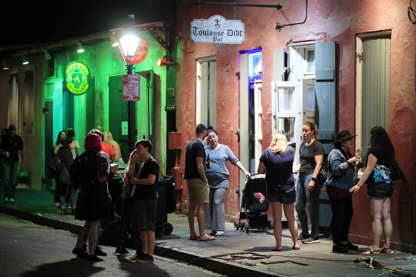 People stand outside a bar just off of Bourbon Street