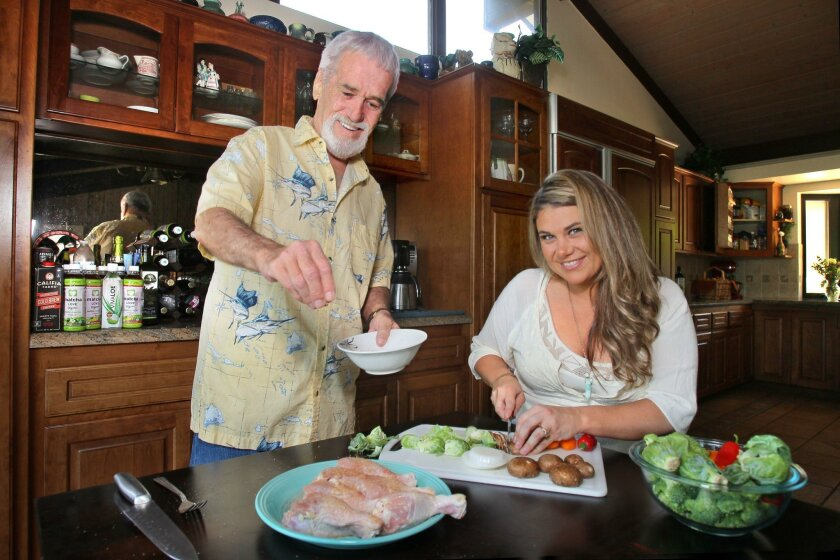 "Portrait of father and daughter chefs Bill and Ashley Travers at their Pauma Valley area home making their ""Chicken Pauma"" dish. Ashley chops mushrooms as Bill seasons the chicken."