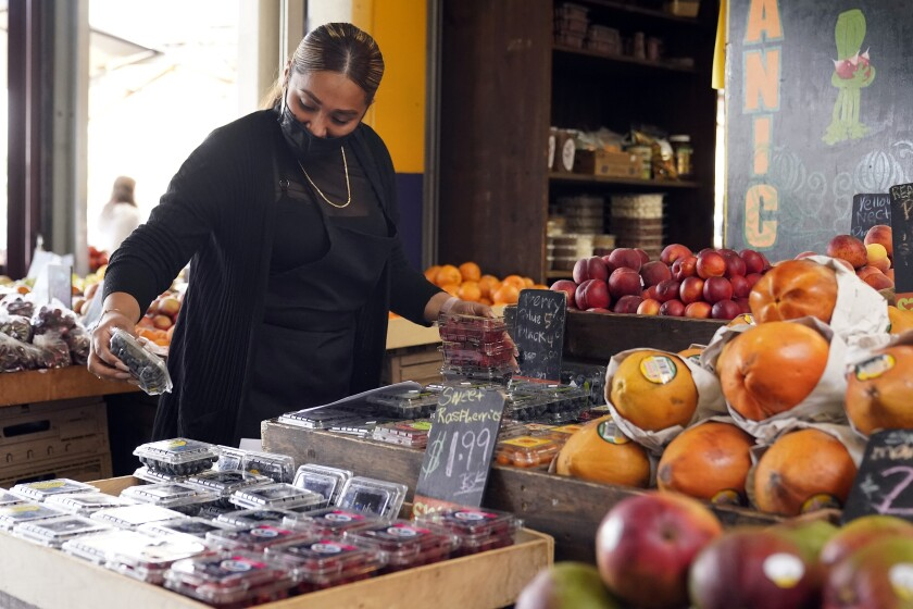 FILE - In this May 20, 2021, file photo, a worker wears a mask while setting up a fruit display amid the COVID-19 pandemic at The Farmers' Market in Los Angeles. Business and agricultural groups are renewing their criticism of new rules adopted by California Gov. Gavin Newsom's workplace regulators. But there is little chance they can quickly change them unless Newsom steps in, which he seemed disinclined to do Friday, June 4. Critics say the rules conflict with the state's broader lifting of masking and other pandemic precautions in less than two weeks. They mean workers will have to wear masks unless every employee in the room is fully vaccinated against the coronavirus. (AP Photo/Marcio Jose Sanchez)