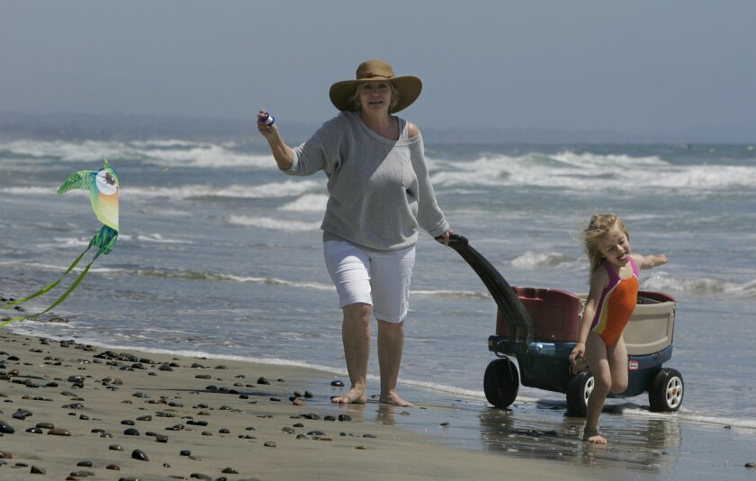 Shari Young of Oceanside tries to fly a kite in the dwindling afternoon breeze as she walks along the beach with her five-year-old friend Dixie Thompson south of the Oceanside Pier.