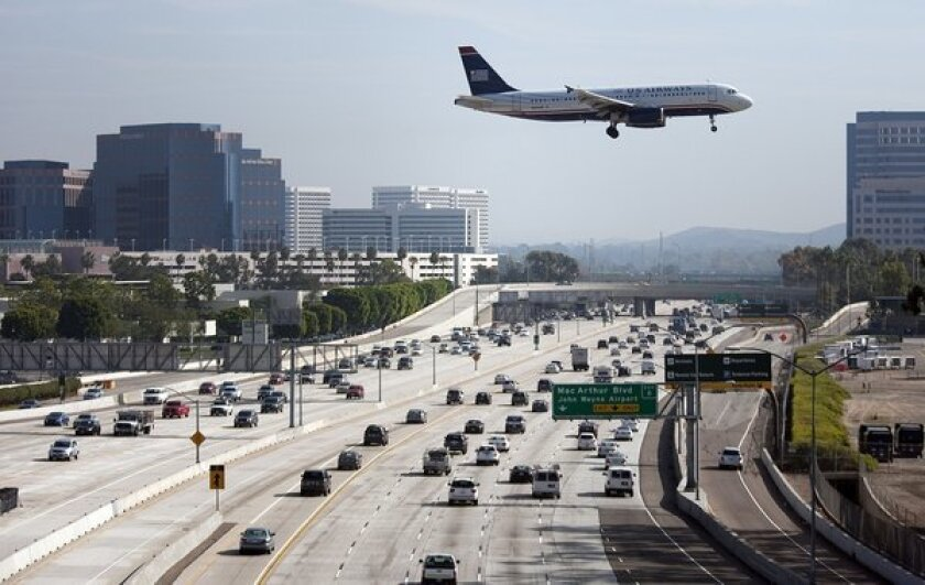 A jet passes over the San Diego Freeway as it approaches John Wayne Airport.