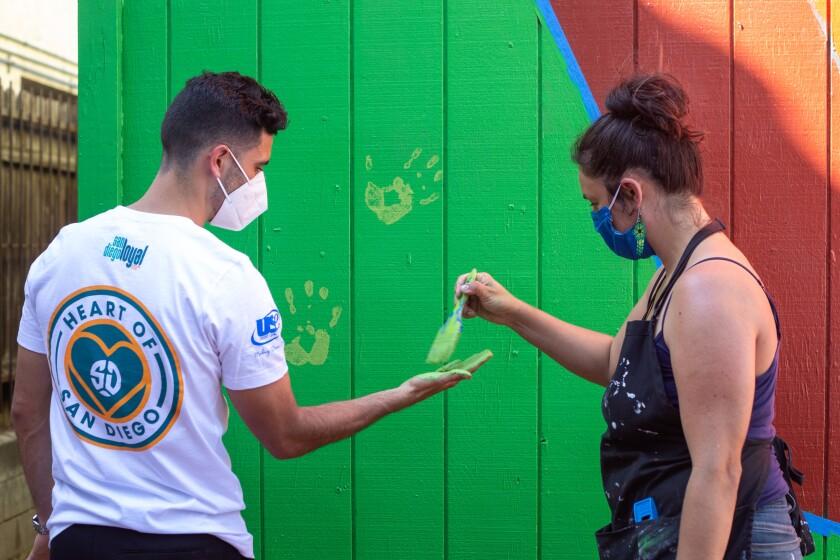 El futbolista Alejandro Guido junto a la artista Yessenia Hulsey en el mural comunitario en Delta Apartments