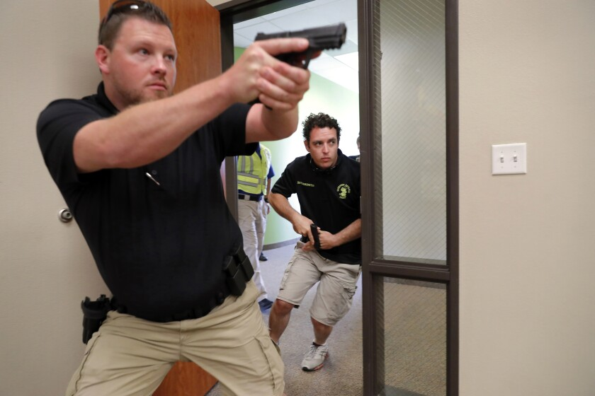 FILE - In this July 21, 2019 file photo, trainees Chris Graves, left, and Bryan Hetherington, right, participate in a security training session at Fellowship of the Parks campus in Haslet, Texas. An industry has sprung up following mass shootings at houses of worship around the country to train civilians to protect their churches with the techniques and equipment of law enforcement. (AP Photo/Tony Gutierrez, File)