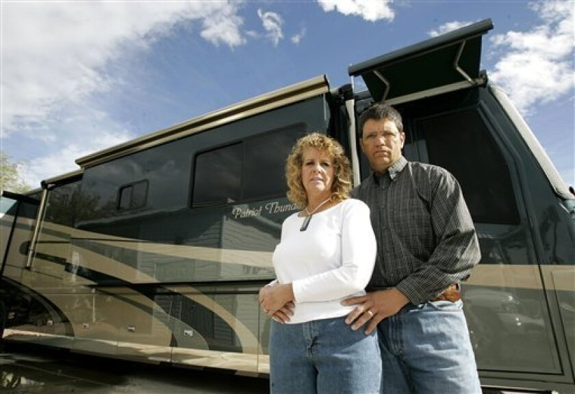 Ronnie Sue Ambrosino and her husband Dominic stand outside their motor home Wednesday, Dec. 17, 2008 in Surprise, Ariz. The money Ronnie entrusted to Bernard Madoff allowed her to retire early, buy a luxury motor home, and travel around the country. Now Ambrosino's among thousands whose fortunes were wiped out by Bernard Madoff, and she's left hoping for a bailout that might never come. (AP Photo/Matt York)