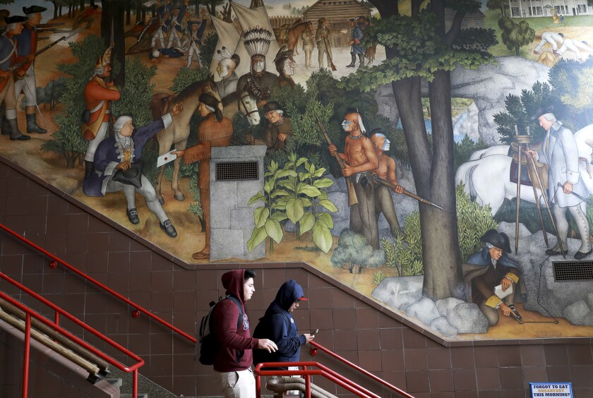 In this photo taken April 3, 2019, a pair of students walk past a historic mural that includes slave