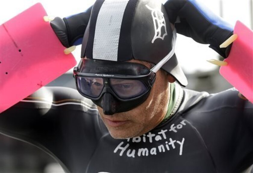 Jim Dreyer, a long-distance swimmer, adjusts his mask before taking off from the Clinton River Boat Club in Clay Township, Mich., Monday, Aug. 5, 2013 to swim 22 miles across Lake St. Clair while hauling dinghies filled with 2,000 pounds of bricks. Dreyer has made direct crossings of each of the five Great Lakes. The event is to raise funds and awareness for Habitat for Humanity. The swim is expected to take 30 hours and end Tuesday at Detroit's Belle Isle. (AP Photo/Carlos Osorio)