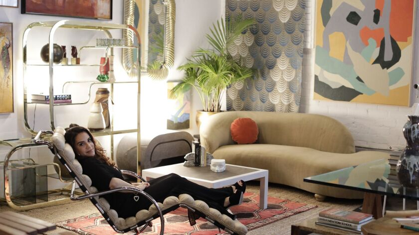 Tricia Beanum reclines on a Mies van der Rohe lounge chair inside her warehouse store Pop Up Home in West Adams.