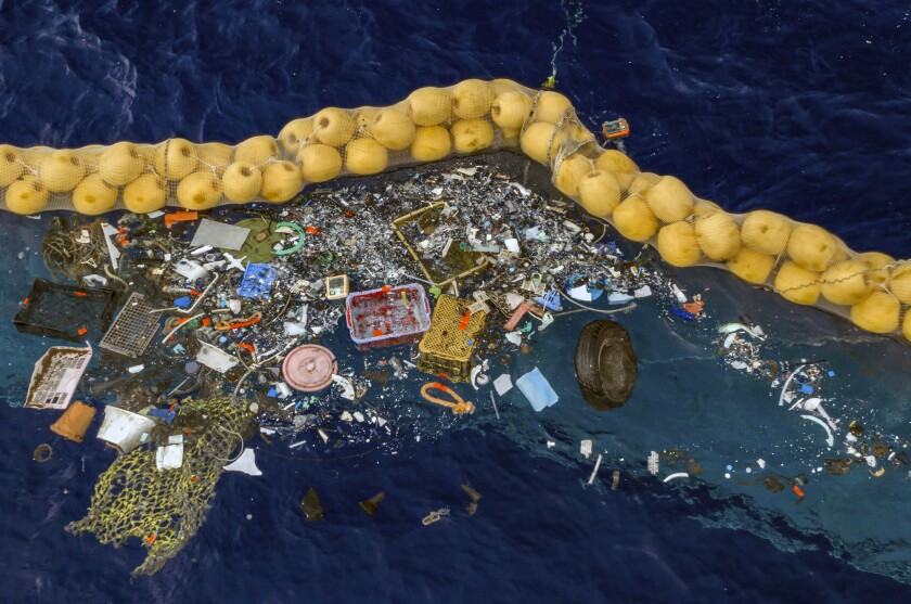 Plastic is retained in front of an extended cork line in the Pacific Ocean.