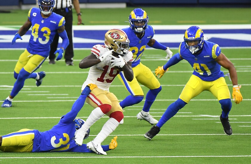 San Francisco 49ers wide receiver Deebo Samuel picks up yards against the Rams in the fourth quarter Sunday.