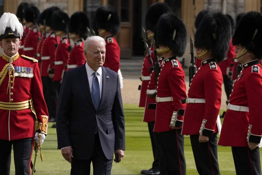 On a green field, Biden walks past a row of men in uniform and bearskins, or tall fur hats.