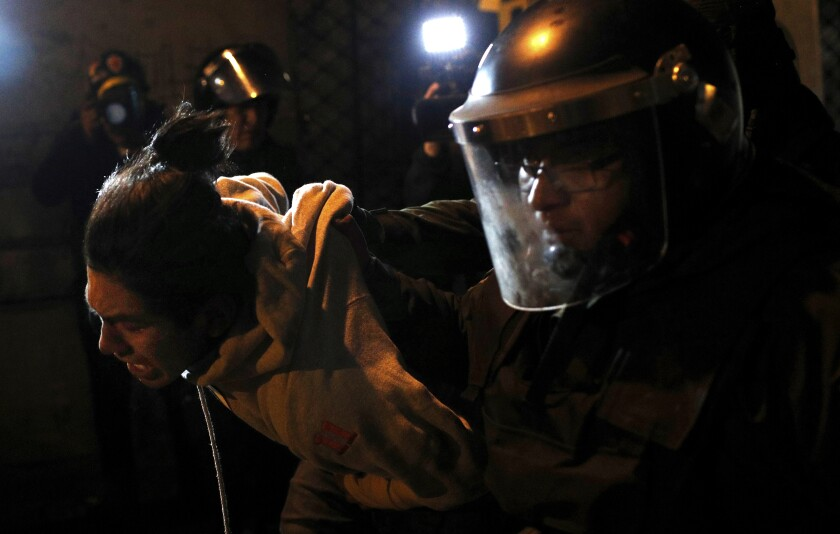 Riot police detain a demonstrator protesting the reelection of President Evo Morales, in La Paz, Bolivia, Thursday, Oct. 31, 2019. Violence has escalated since Morales was declared the winner of the Oct. 20 vote amid delays in the vote count. The opposition alleges the outcome was rigged to give Morales enough of a majority to avoid a runoff election; the president denies any irregularities. (AP Photo/Juan Karita)