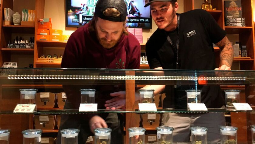 Torrey Holistics employees Matt Sullivan, left, and Taron McElroy arrange jars of cannabis at the San Diego store in December, when it became the first to get a state license to sell marijuana for recreational use.