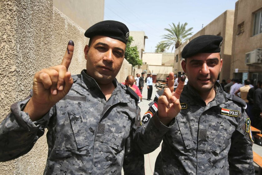 Iraqi police officers show their inked fingers at a polling center in Baghdad, Iraq, Monday, April 28, 2014. Iraqi officials say suicide bombers have targeted polling centers as soldiers and security forces cast ballots ahead of parliamentary elections. (AP Photo/ Karim Kadim)