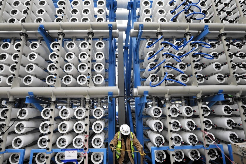 A worker climbs stairs among pressure vessels that convert seawater into fr