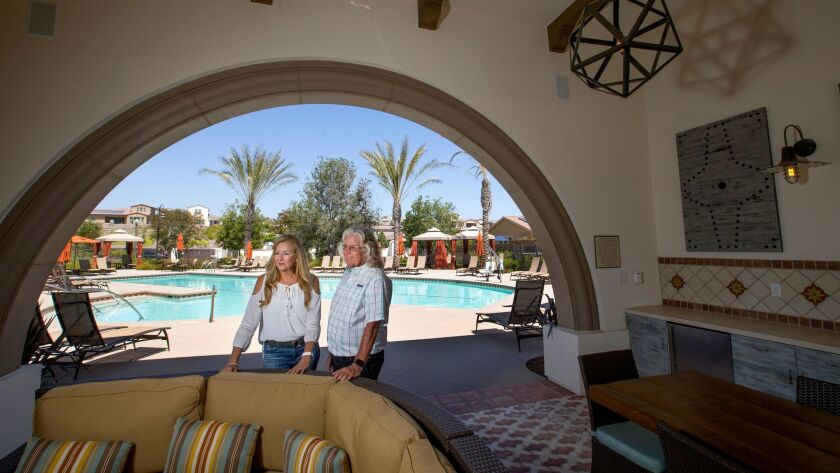Pam Watkins and husband Craig stand near one of the seniors-only pools at Rancho Mission Viejo, a multi-generational community in South Orange County.