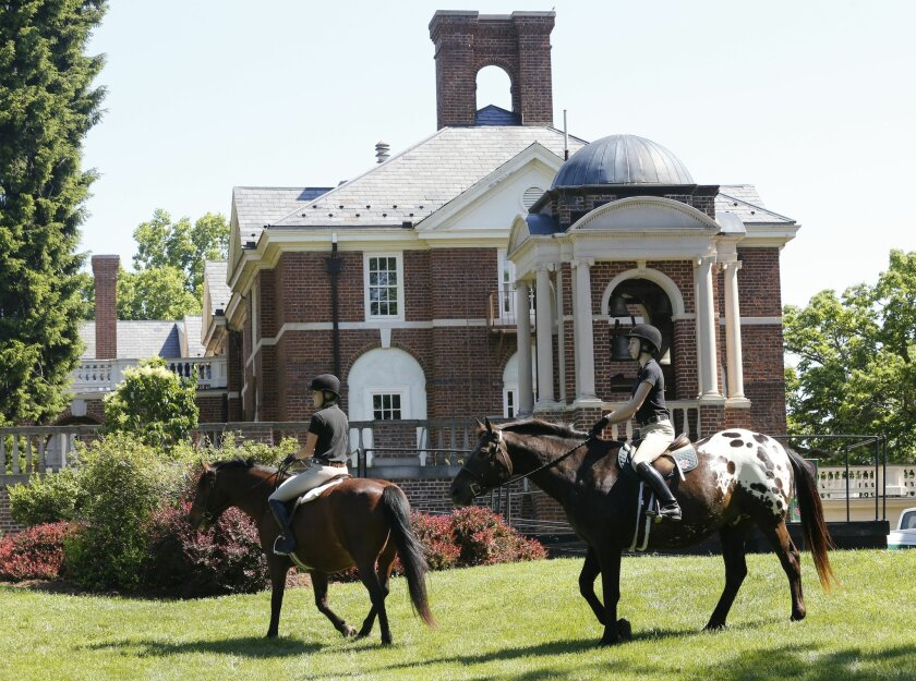 FILE- In this May 13, 2015, file photo, graduating seniors at Sweet Briar college participate on the tradition Senior ride on the quad at the school in Sweet Briar, Va. Virginia's attorney general announced a mediated settlement Saturday, June 20, to keep open Sweet Briar College, using $12 million