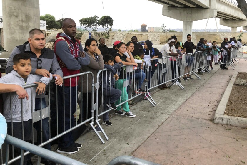 In this Sept. 26, 2019, file photo, asylum seekers in Tijuana, Mexico, listen to names being called from a waiting list to claim asylum at a border crossing in San Diego.