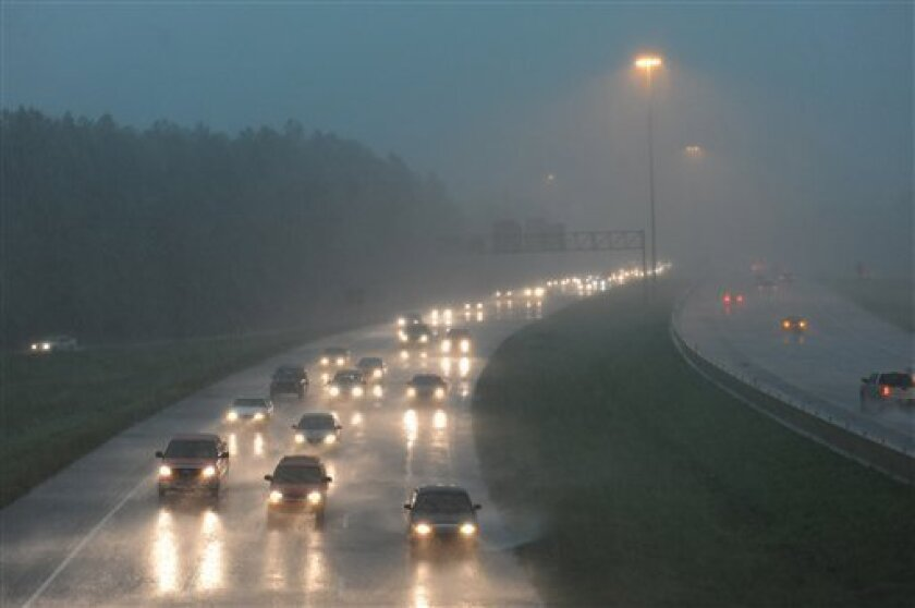 Motorists traveling Interstate 55 south at Fortification Street get pelted by heavy rain from the west as a line severe weather, bringing with it tornado warnings, moves through the metro area in Jackson, Miss, Monday, April 4, 2011. (AP Photo/The Clarion-Ledger, Barbara Gauntt)