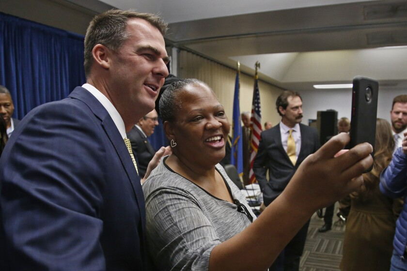 Oklahoma Gov. Kevin Stitt, left, poses for a selfie with Joy Block, right, of Tulsa, Okla., following a news conference to announce that Oklahoma will release more than 400 inmates after the board approved what they say is the largest single-day mass commutation in U.S. history, Friday, Nov. 1, 2019, in Oklahoma City. Block is the founder of Walters Way Regaining Your Life Foundation, a Tulsa re-entry program for offenders. (AP Photo/Sue Ogrocki)