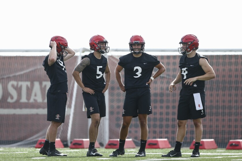 San Diego State starting quarterback Ryan Agnew (left) talks with Mark Salazar, Carson Baker, and Jordon Brookshire (left to right), who are all competing to be the team's backup quarterback this season.