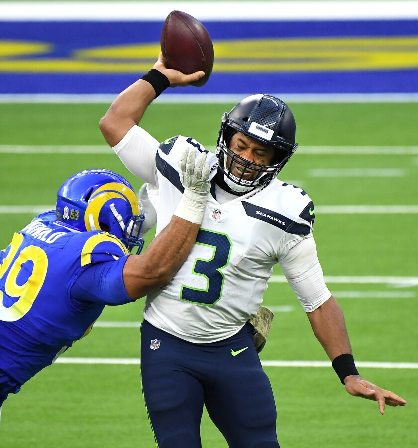 Rams Aaron Donald hits Seahawks quarterback Russell Wilson as he prepares to throw a pass.