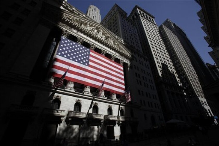 In this June 2, 2011 photo, American flags are displayed on the New York Stock Exchange in New York. Global stocks took another pounding Tuesday, July 12, 2011, while borrowing costs for Spain and Italy spiked higher as investors worried that Europe's debt crisis could infect the continent's larger economies.(AP Photo/Seth Wenig)