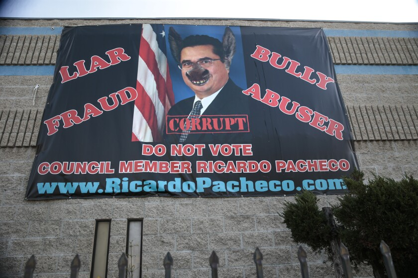 A banner with an image of a councilman with donkey ears and a nose, with the words liar, fraud, bully, abuser, corrupt
